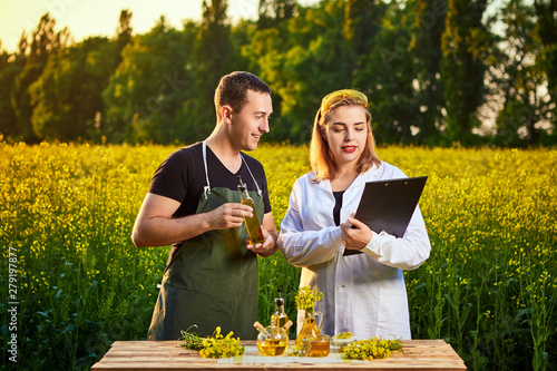 Fototapeta Agronomist woman and farmer examine rapeseed oil and blossoming rape (canola) field using tablet obraz