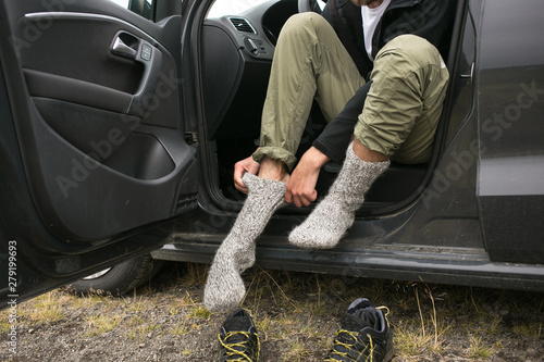 Adventurer, touirst or hiking affectionate changes shoes inside car after or before long wet walk in harsh conditions. Puts on pair or clean and dry wool socks to warm up feet in cold weather - 279199693