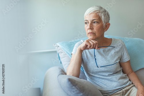 Fototapeta Feeling Down. Middle aged woman in glasses looking down. Portrait of pensive worried senior woman looking through the window and thinking. Pensive woman. obraz