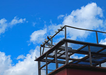 Domestic Doves In Dovecote Against The Blue Sky With Clouds. Pigeons Sitting On Old Latticed Dovecote From Steel Rods