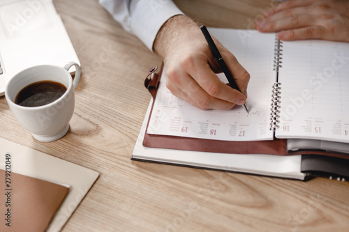 Obraz Man writing in daily planner with black pen - fototapety do salonu