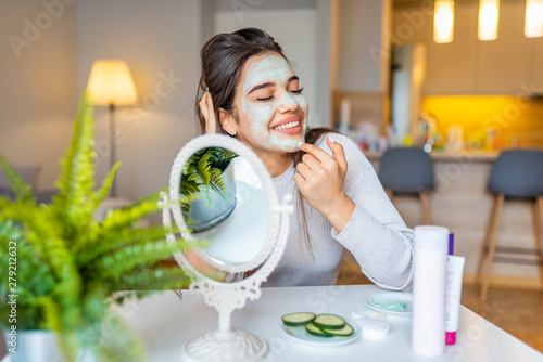 Leinwand Poster Young woman with cleansing mask on her face at home