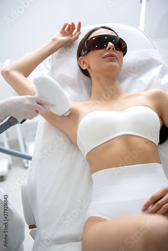 Smiling lady on armpit laser epilation procedure Canvas Print