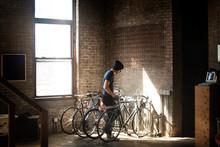 Young Man Locking Bicycle In Rack