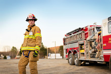 Firefighter Standing In Front Of Fire Engine