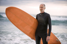 Senior Man With Surfboard Standing On Beach