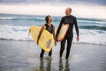View Of Senior Surfers Wearing Wetsuits