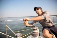 Man Adjusting Sails Of Yacht