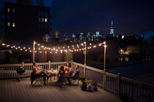 Group Of Friends Sitting On Roof Terrace