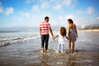Parents with daughter (4-5) walking on beach