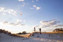 Couple Playing With Kite On Sa...