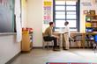 Teacher talking to schoolboy in classroom