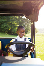 Portrait Of Boy Driving Golf Cart