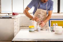 Man Painting Wood In Workshop