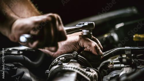 Fototapeta Auto mechanic working on car engine in mechanics garage. Repair service. obraz