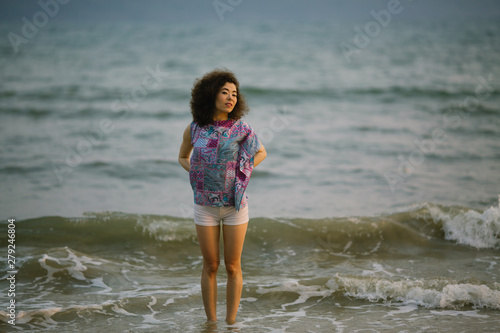A young woman of mixed race stands in the waves on the surf line on the sea beach.