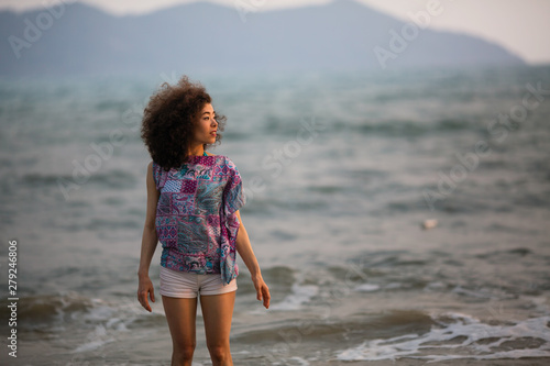 Young woman of mixed race stands in the waves on the surf line on the sea beach.
