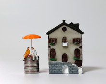 A Miniature Old Couple Sitting On A Pile Of Coins With An Orange Umbrella Next To A Miniature House.