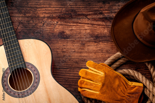 American culture, living on a ranch and country muisc concept theme with a cowboy hat, acoustic guitar, farm gloves and a rope lasso on a wooden background in a old saloon with copy space - 279256451