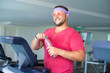 Funny fat male in pink glasses and in a pink t-shirt is engaged on a treadmill in the gym depicting a girl. man drinking water on a treadmill