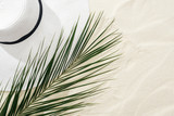 top view of white straw hat and green palm leaf on sand