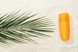 top view of palm leaf and orange sunscreen spray on sand