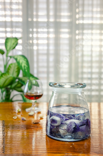 Fototapeta Preparing gem elixir to get over the hangover. Amethyst and clear quartz placed in a glass jar and filled with natural spring water. After the stones give energy to it, can use this homeopathic remedy obraz