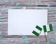 October 1, happy independence Day of Nigeria. the concept of patriotism , freedom and independence. Mini paper flags with yellow and red confetti white card on wooden background