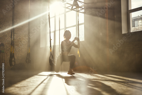 Fototapeta Deep squat. Full-length of young athletic woman in sports clothing training legs with trx fitness straps in the gym obraz