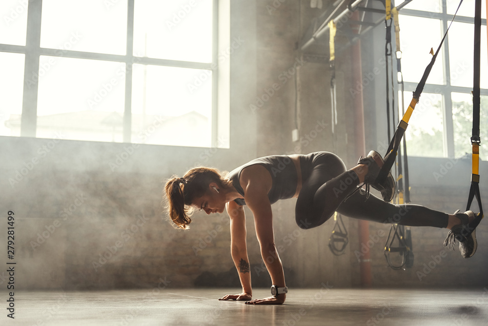 Fototapety, obrazy: TRX Training. Young athletic woman in sports clothing training legs with trx fitness straps in the gym.