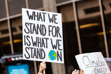Environmentalist Sign At Demonstration. A Slogan On An Activist's Placard Reads What We Stand For Is What We Stand On During An Environmental Protest. Handmade Sign By An Environment Demonstrator.