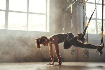 TRX trening. Mlada atletska žena u sportskoj odjeći koja trenira noge s trx fitnes trakama u teretani.