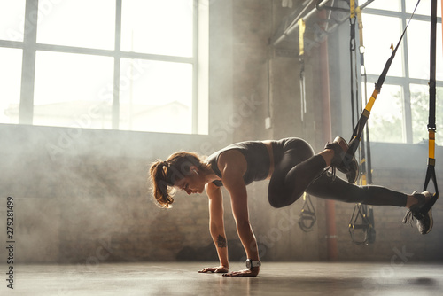 TRX Training. Young athletic woman in sports clothing training legs with trx fitness straps in the gym.
