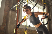 Perfect Push-up. Side View Of Young Athletic Woman With Perfect Body In Sportswear Doing Push Ups With Trx Fitness Straps In The Gym.