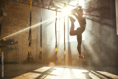 Perfect flexibility. Full length of athletic woman in black sport clothing jumping while exercising in professional semi-dark gym.