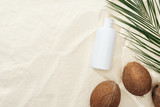 top view of palm leaf, coconuts and sunscreen product on sand
