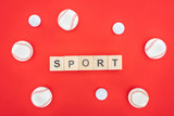 sport lettering on wooden cubes near softballs isolated on red