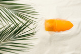 top view of sunscreen and green palm leaves on golden sand