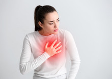 Young Woman Suffering From Heart Attack On Light Background