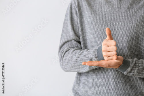 Valokuva  Young deaf mute man using sign language on light background