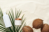 top view of palm leaves, coconuts and cosmetics on sand