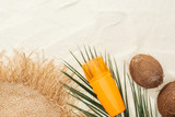 top view of palm leaf, orange sunscreen, coconuts and straw hat on sand