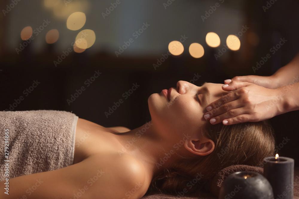 Fototapeta Beautiful young woman receiving facial massage in spa salon