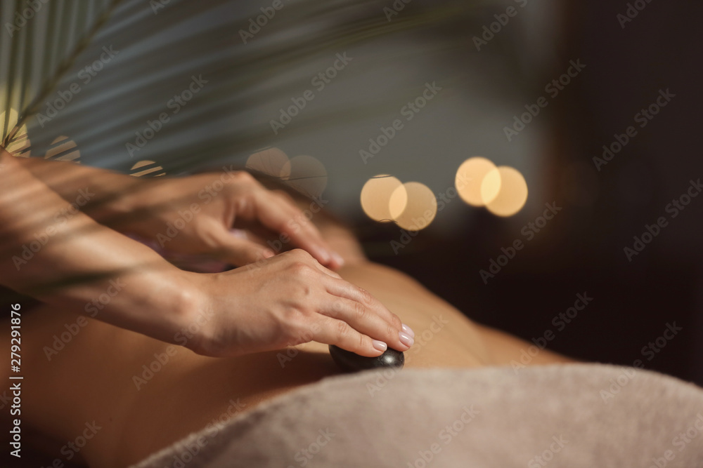 Fototapeta Beautiful young woman undergoing treatment with hot stones in spa salon