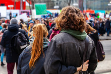 People Gather For Climate Change. Two Young People Are Seen From The Back, Watching A Crowded Demonstration Of People Against Global Warming On A Street In Montreal, Canada
