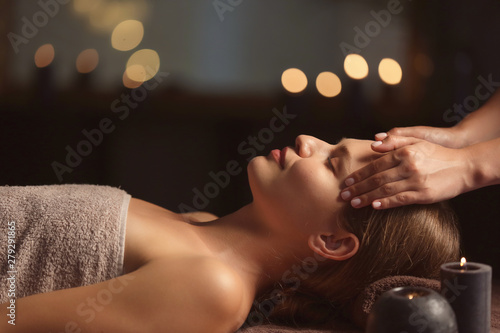 Beautiful young woman receiving facial massage in spa salon