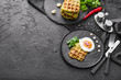 Plate with tasty squash waffles and fried egg on dark table