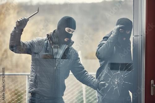 Cuadros en Lienzo  Einbrecher mit Brecheisen schlagen Glas ein