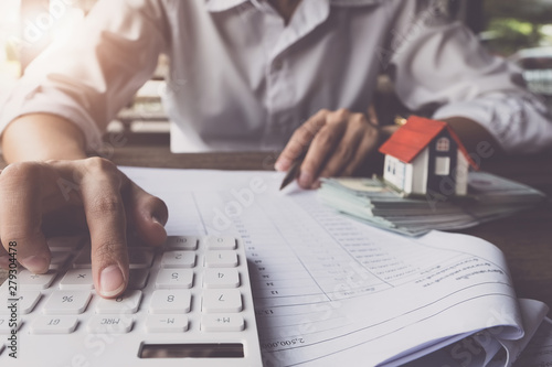 Fotografia  Customers use pens and calculators to calculate home purchase loans according to loan documents received from the bank