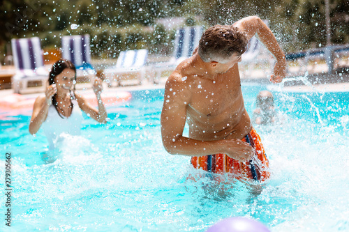 Fototapeta  Dark-haired husband splashing water on wife in swimming pool